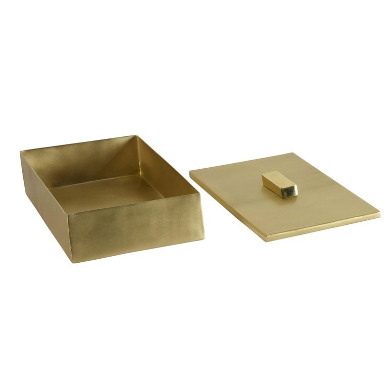 A handmade angled brass box featuring a matte finish and a contrasting shiny nob.