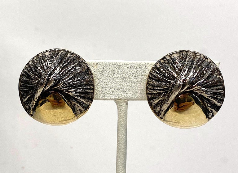 Hand made pair of abstract modernist earrings in sterling silver with gold plate. The dome button style earrings have a sculptural quality with a patinated sterling twist design . Next to the twist is a gold plate area which nicely compliments the