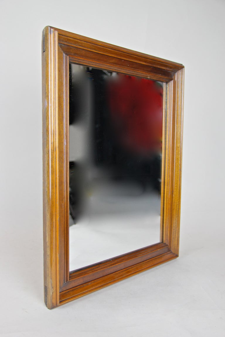Beautiful Biedermeier Nutwood wall mirror out of Austria from circa 1860, the second period. This mid-sized 19th century wall mirror features great carved nut wood bars over an overlapped inserted substructure. The straight design alongside the