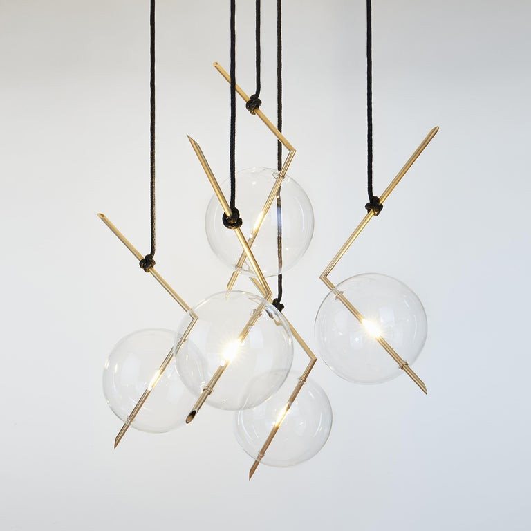 Nuvola five-light floats in space like a jewel hanging from the ceiling, hooked at the end of a leather cord that has been hand knotted around the brass tube; a perfect equilibrium of different materials, with obsessive attention to details.  The