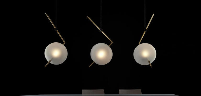 Nuvola contemporary pendant light floats in space like a jewel hanging from the ceiling, hooked at the end of a leather cord that has been hand-knotted around the brass tube; a perfect equilibrium of different materials, with obsessive attention to