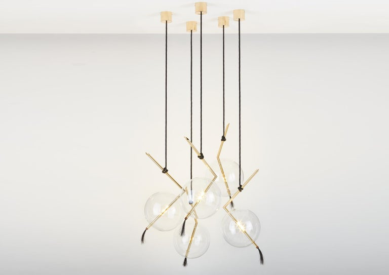 Nuvola Five Lights floats in space like a Jewel hanging from the Ceiling, hooked at the end of a Leather Cord that has been hand-knotted around the brass tube; a perfect equilibrium of different materials, with obsessive attention to details.  The