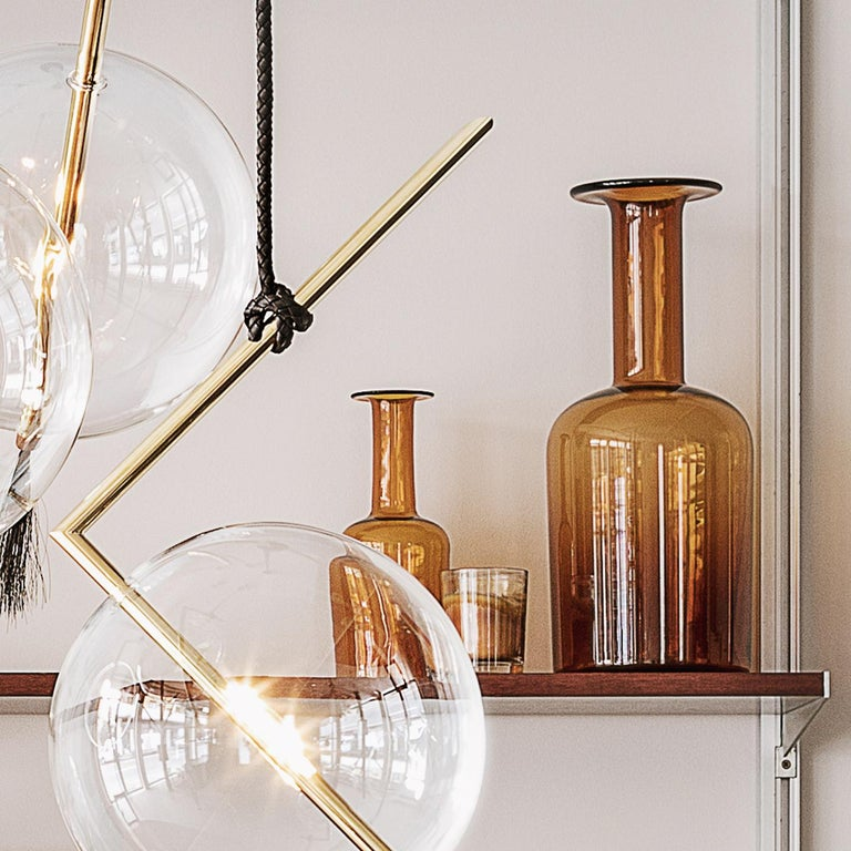 Marked by a streamlined silhouette and unconventional design, this exceptional light pendant will be a radiant touch in any interior. The set of five pendant lights boast a Minimalist shape, defined by a bent brass tube, accented with a hand blown