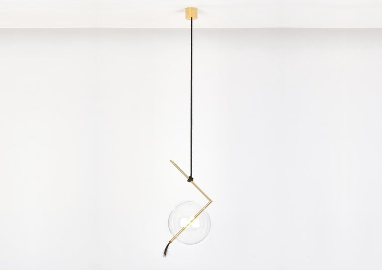 Nuvola pendant floats in space like a jewel hanging from the ceiling, hooked at the end of a leather cord that has been hand-knotted around the brass tube; a perfect equilibrium of contrasting materials, with obsessive attention to details.