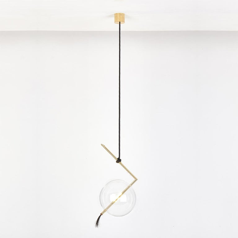 Arranged in multiples at different heights in a minimalist living room or dining room, this refined light pendant is a radiant, sculptural statement piece. The unconventional silhouette is made of a machined brass tube bent at a right angle, the top