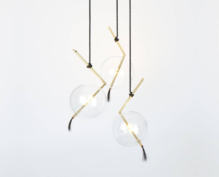 Nuvola Three Lights Customizable Chandelier or Pendant light-fixture floats in space like a Jewel hanging from the Ceiling. The pure Geometry of the Brass Rod containing the led light contrasts with the ephemeral transparency of the Handblown