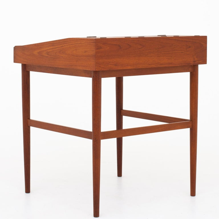 NV 40, writing desk made of teak, large writing plate with handle of a slightly keeled edge, three smaller plates with handles of brass. Maker Niels Vodder.