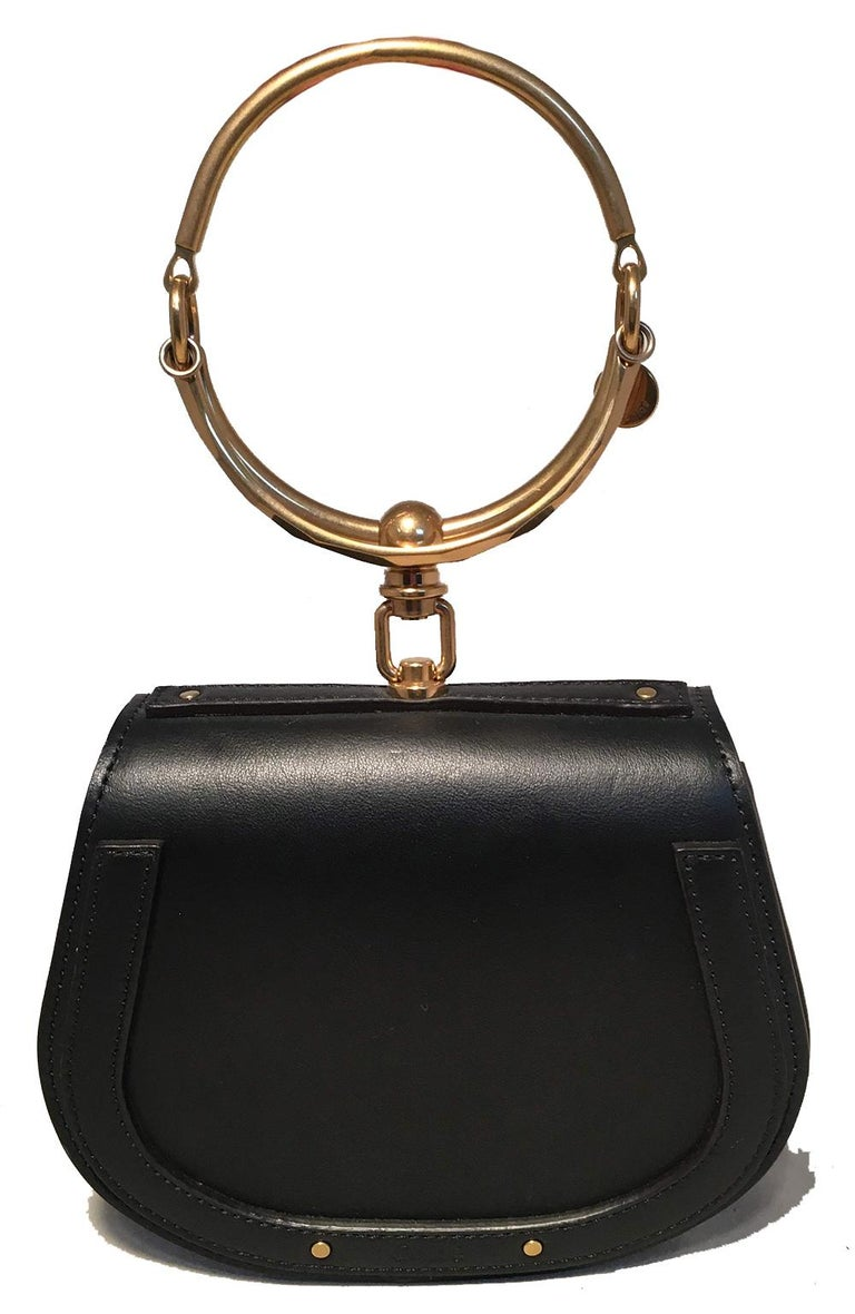 NWOT Chloe Nile Small Black Leather Bracelet Bag in unused condition. Black smooth leather exterior trimmed with matte gold hardware. Unique hoop bracelet top handle. Back side slit pocket. Front flap snap closure opens to a suede interior that