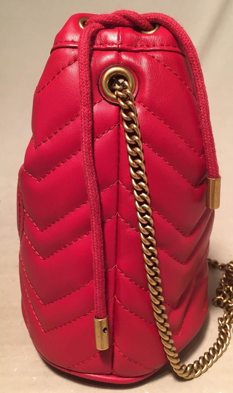 Gucci GG Marmont Mini Quilted Red Leather Bucket Bag in NWOT condition. Red chevron quilted leather exterior trimmed with bronze hardware. Signature bronze GG gucci logo along front side and adorable quilted heart along back. Removable bronze chain