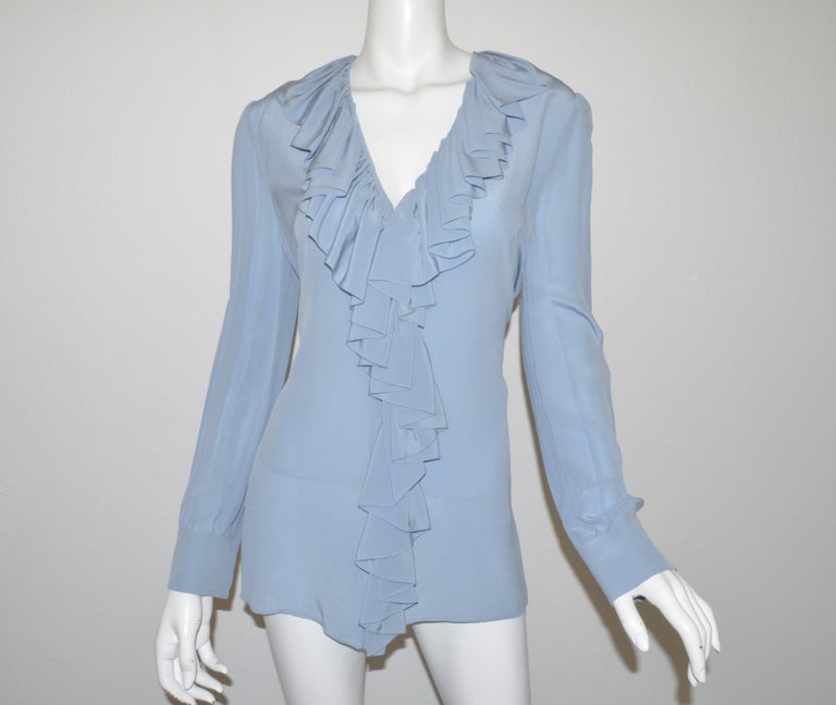 Gucci blouse featured in a powder blue color with concealed button closures, ruffled collar, and pearl buttons on the cuffs. Blouse is a size 44, composed with   Measurement: Bust 42'' Sleeve 25'' Length 28'' Shoulder to shoulder 15''