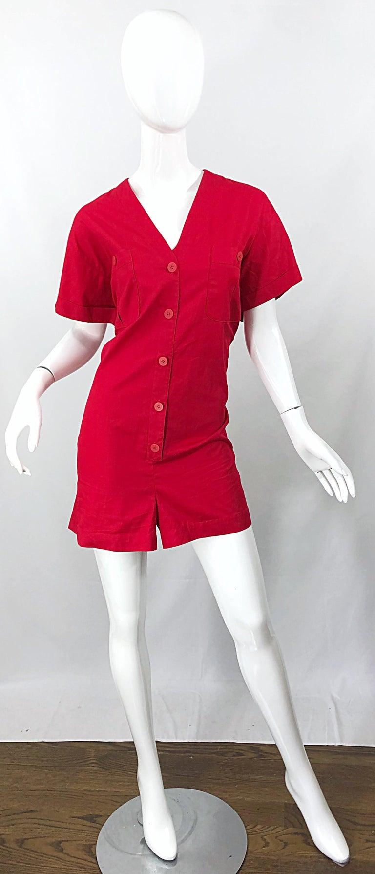 Brand new with tags CHIRSTIAN DIOR romper / jumpsuit in rare Size 14 ! Soft cotton lipstick red fabric buttons up the front, and at each breast pocket. Flattering v-neck collar with cuffed sleeves. Pockets also at each side of the waist. Can easily