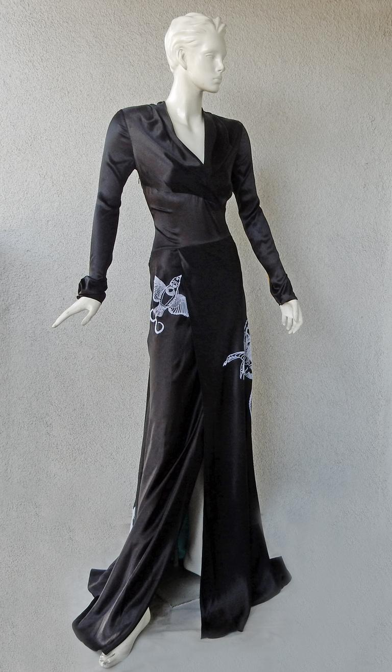 Vionnet rich black deco inspired gown.   Features bias cut full skirt accented with a panel of deep blue turquoise;  Large flocked birds (possibly swallows) strategically placed.  V neck bodice with asymmetric inserted panel waistband; long wrist