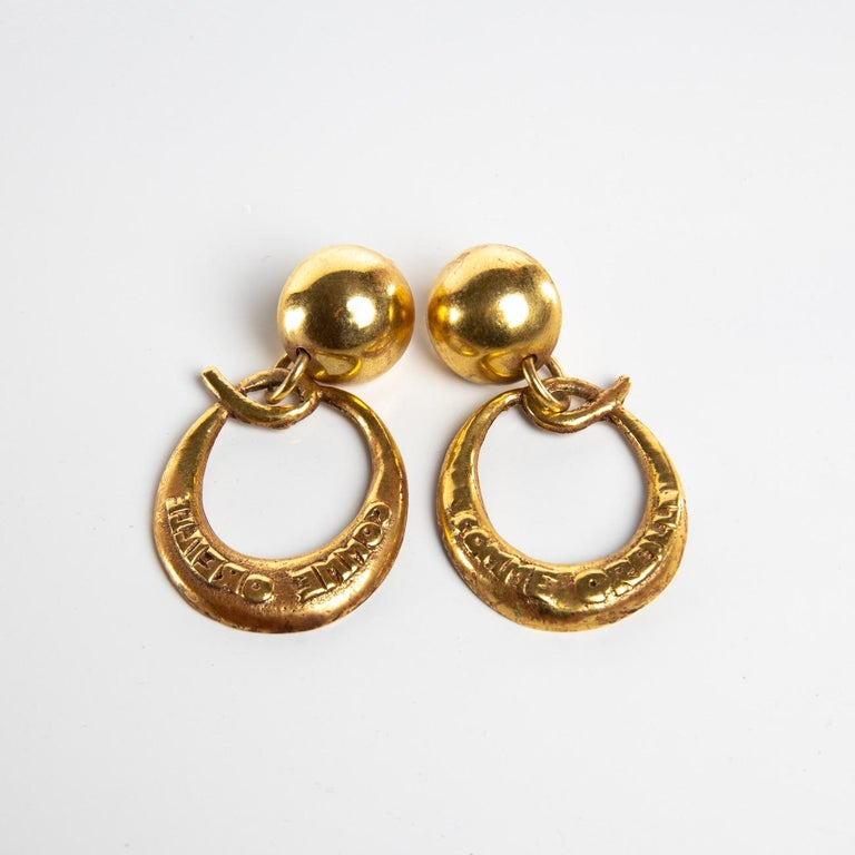 This pair of clip-on earrings is made of gilded bronze balls on which are suspended a large letter