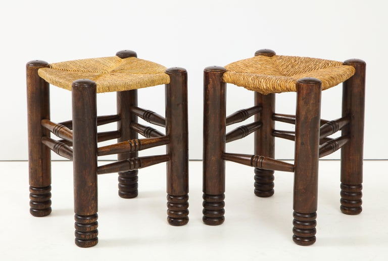 These rustic oak and straw stools designed by Charles Dudouyt in the 1930s are composed of 4 cylindrical solid oak legs linked by sleepers and a square braided straw seat. In excellent vintage condition, they have developed a beautiful patina over