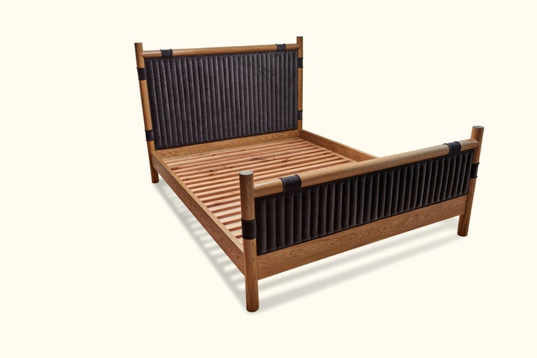 The Chiselhurst Bed is an upholstered bed with a solid American walnut or white oak frame finished with brass caps. Slats are provided. Shown here in oiled oak