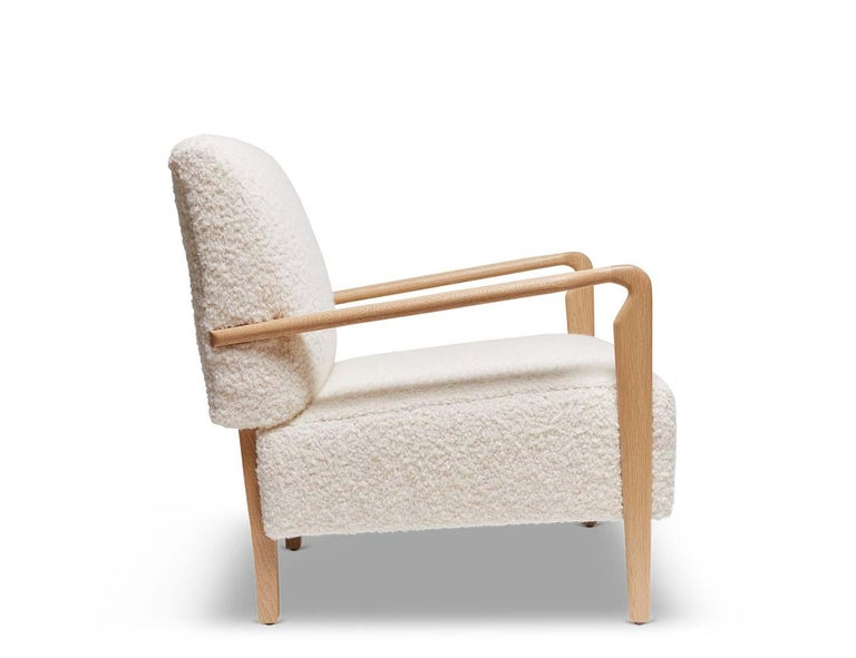 The Niguel lounge chair is a French inspired design with a sculptural solid wood frame and an upholstered seat. Shown here in Natural Oak and White Alpaca Bouclé.  The Lawson-Fenning collection is designed and handmade in Los Angeles,