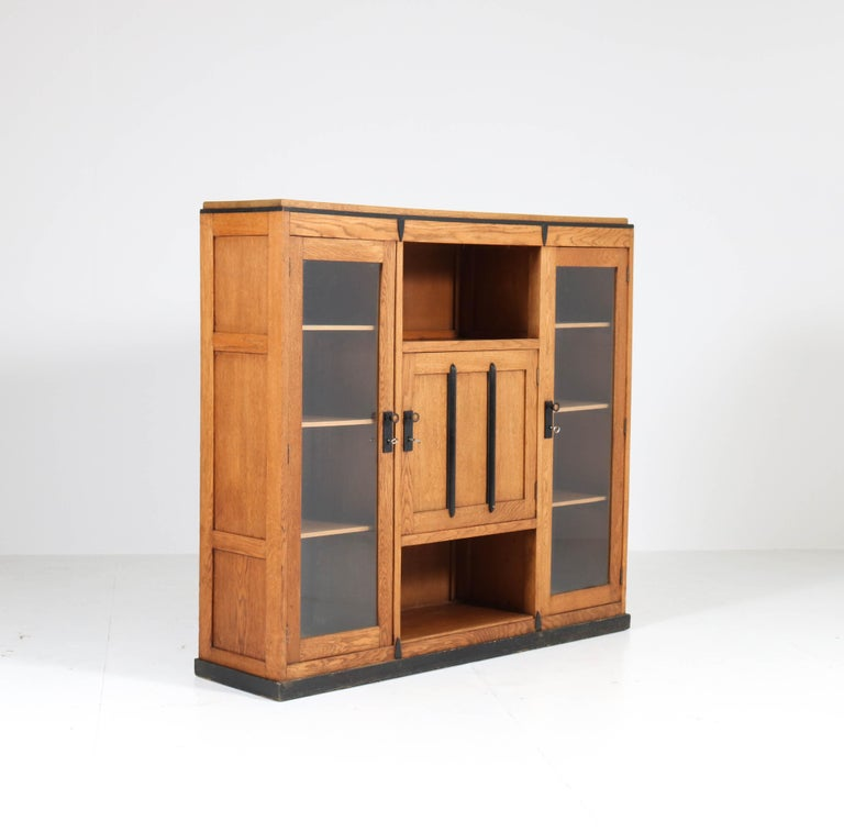 Wonderful and rare Art Deco Amsterdam School bookcase. Striking Dutch design from the 1920s. Solid oak with original ebonized lining. Seven original oak shelves, adjustable in height. In good original condition with minor wear consistent with