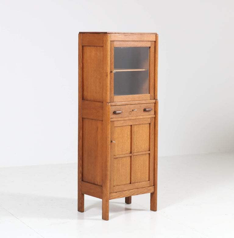 Wonderful and rare Art Deco Amsterdam School cabinet. Striking Dutch design from the twenties. Solid oak with solid ebony Macassar knobs on the drawer. Three locks and keys in good working order. In good original condition with minor wear