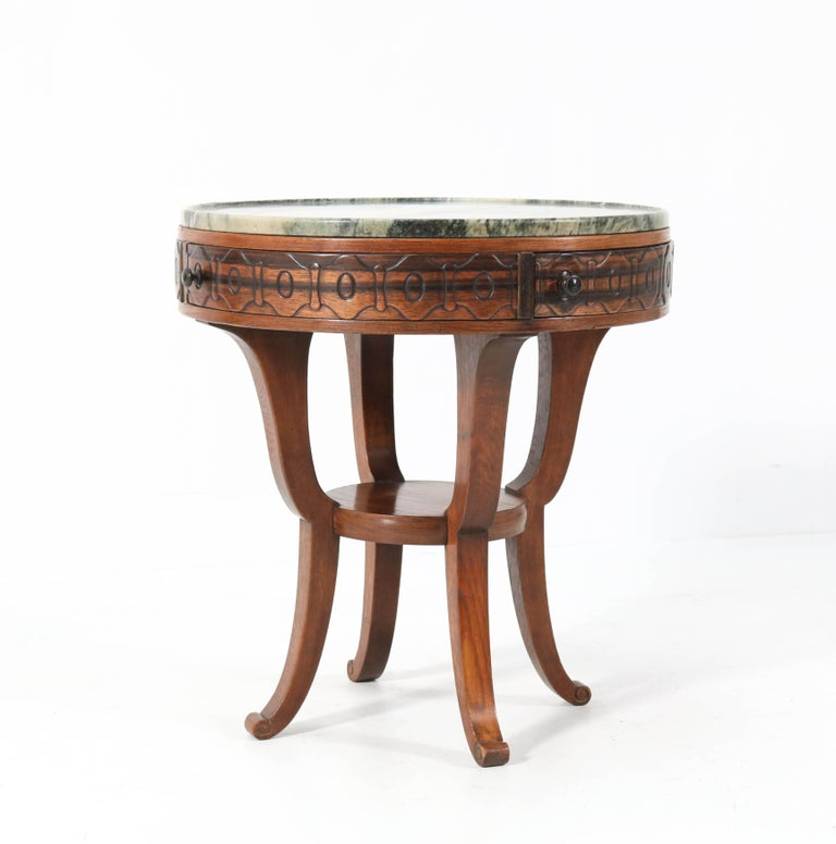 Stunning and rare Art Deco Amsterdam School coffee table. Design by 't Woonhuys Amsterdam. Striking Dutch design from the 1920s. Solid oak with four Macassar ebony veneered drawers and solid knobs. Original green marble top. Marked with