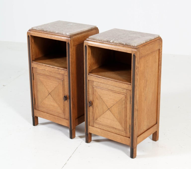 Wonderful and rare pair of Art Deco Amsterdam School nightstands. Striking Dutch design from the 1920s. Solid oak with solid ebony Macassar handles and lining. The pair has the original marble tops and they are in very good shape. In very good