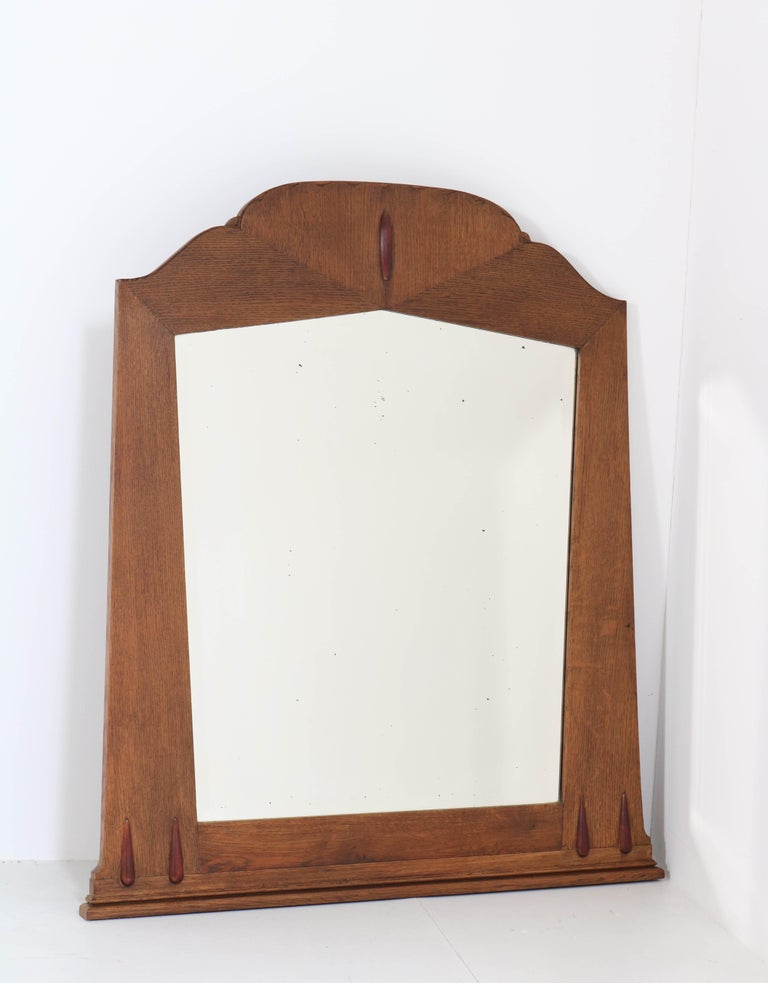 Stunning and rare Art Deco Amsterdam School wall mirror. Design by Fa. S. Speelman Rotterdam. Striking Dutch design from the twenties. Solid oak frame with original beveled mirrored glass. In very good original condition with minor wear (the
