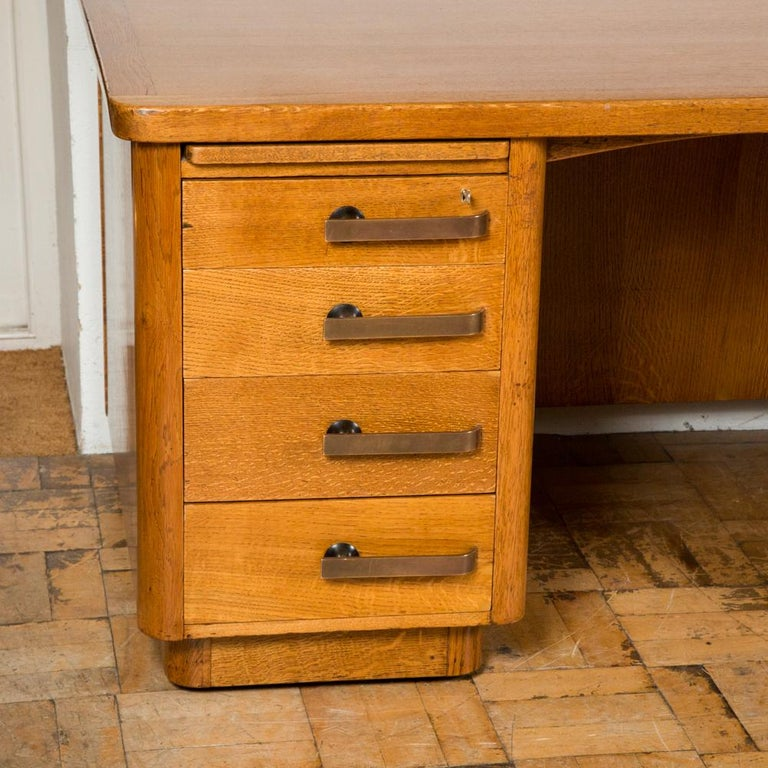 A freestanding oak Art Deco style pedestal desk with bronze handles by Abbess.  Each pedestal having one writing slide over four drawers with bronze handles, the top drawer on each side locks.  Abbess Furniture was established by Charles Nash
