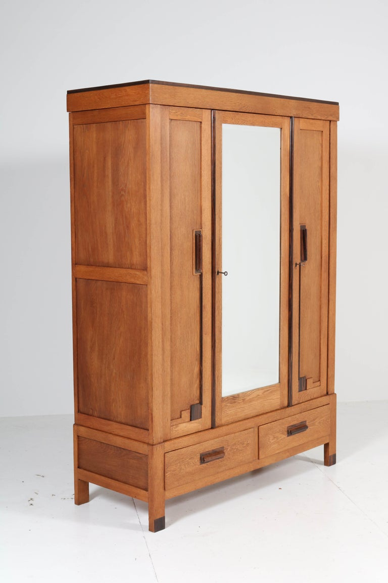 Wonderful Art Deco Haagse School armoire or wardrobe. Striking Dutch design from the twenties. Oak with solid Macassar ebony handles. The brass bar for hanging clothes is behind the left door and the door with the original beveled