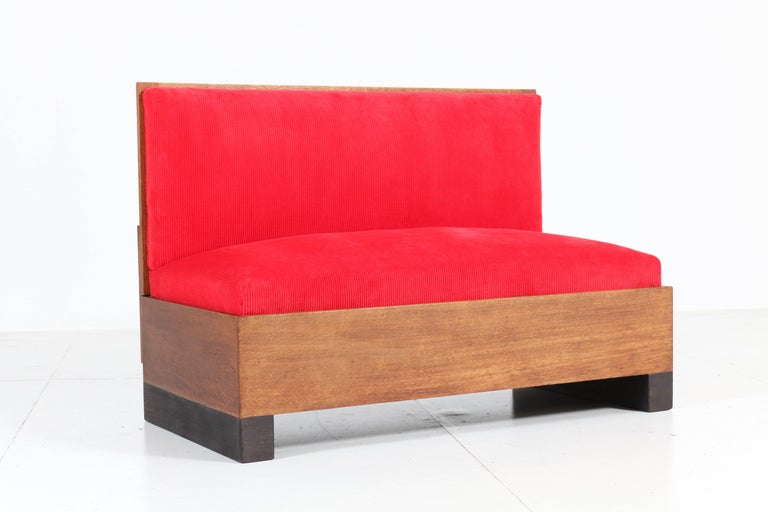 Wonderful and rare Art Deco Haagse School bench or sofa. Design by Willem Penaat for Metz & Co. Amsterdam Striking Dutch design from the thirties. Solid oak frame with black lacquered lining and re-upholstered with red Manchester