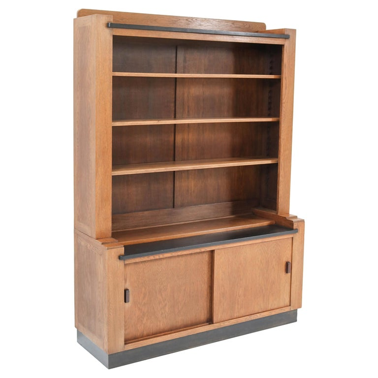 Magnificent and rare Art Deco Haagse School bookcase. Design by Cor Alons for L.O.V. Oosterbeek. Striking Dutch design from the 1920s. Solid oak with original Macassar ebony handles. Original black lacquered lining. Three original solid oak