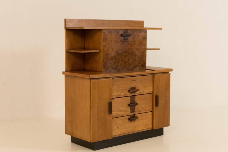 Oak Art Deco Haagse school bookcase with drop-front desk. Design by P.E.L.Izeren for Genneper Molen. Striking Dutch design from the twenties. Solid ebony Macassar handles on doors and drawers. The veneer on the drop-front is made from walnut and