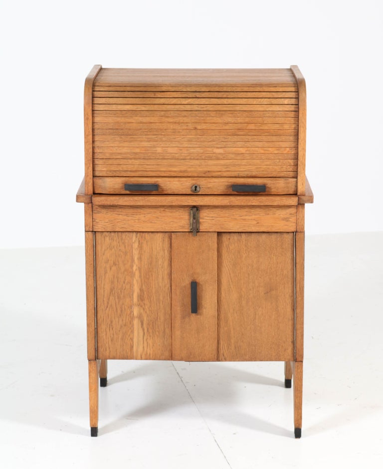 Rare and hard to find Art Deco Haagse School roll top desk. Solid oak with ebonized handles. Striking Dutch design from the 1920s. By pulling down the roll top at the back, this stunning piece of furniture transforms in a pedestal desk! Width of