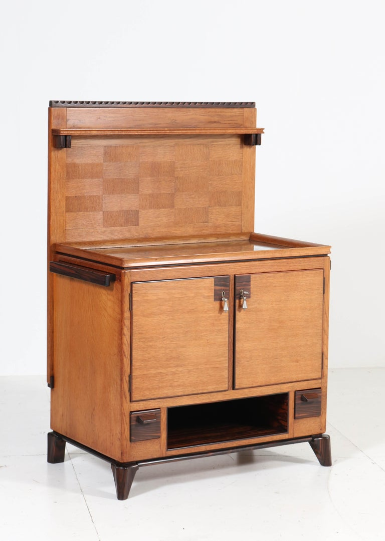 Magnificent and very rare Art Deco Haagse School serving cabinet. Design by Anton Lucas Leiden. Striking Dutch design from the twenties. Oak with ebony macassar top and original oak/glass serving tray. Four original solid ebony macassar