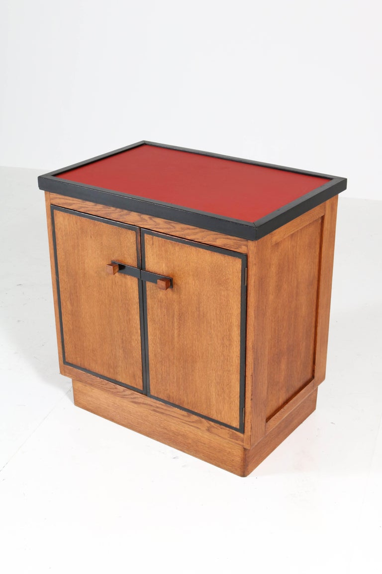 Magnificent and rare Art Deco Haagse School tea cabinet. Design by Jan Brunott. Striking Dutch design from the twenties. Solid oak and oak veneer with original ebonized lining. The top of the tray is renewed with red linoleum. Marked with