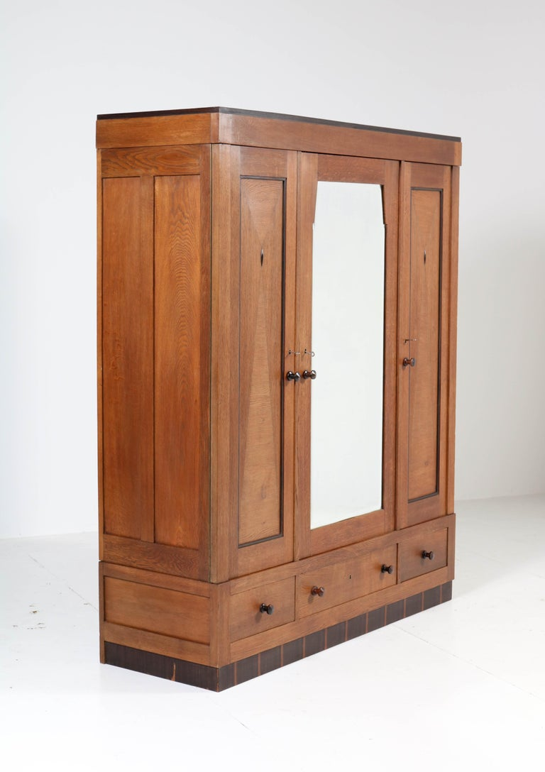 Wonderful Art Deco Haagse School wardrobe or armoir. Striking Dutch design from the twenties. Oak with ebony Macassar knobs and lining. Behind the door with the original beveled mirror you will find three original wooden shelves. The other
