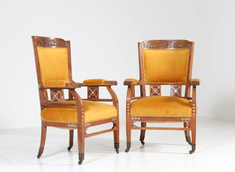 Magnificent and rare pair of Art Nouveau Arts & Crafts armchairs. Design by H.F. Jansen en Zonen, Amsterdam. Striking Dutch design from the 1900s. Solid oak with carved armrests and inlay. Re-upholstered with velvet fabric. In very good