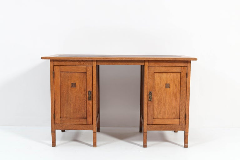 Stunning Art Nouveau Arts & Crafts pedestal desk. Striking Dutch design from the 1900s. Solid oak with original brass handles. The top has a new faux leather writing section. This wonderful piece of furniture can be dismantled into three pieces