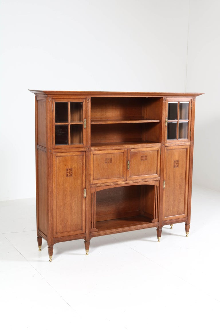 Magnificent and rare Arts & Crafts Art Nouveau bookcase. Striking Dutch design from the 1900s. Solid oak with beveled glass and inlay. On six original solid brass feet. In very good original condition with minor wear consistent with age and