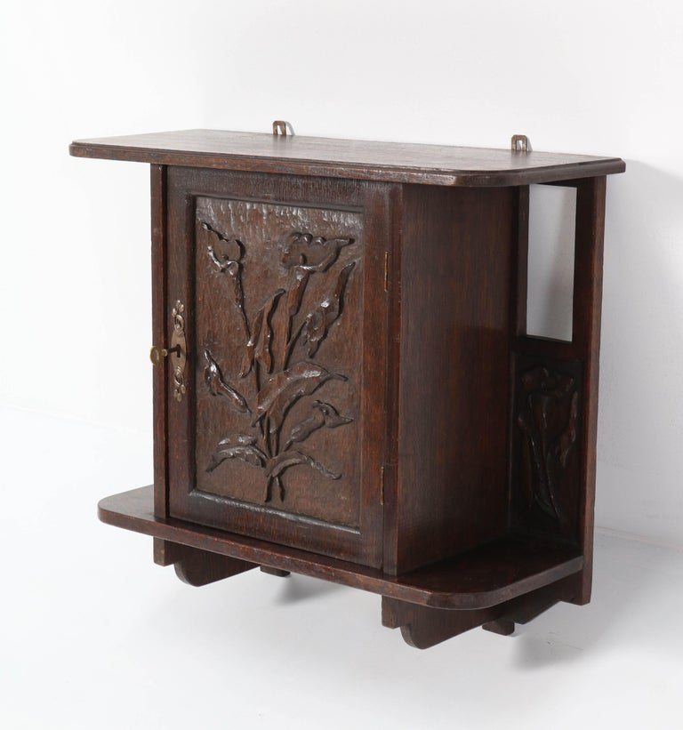 Magnificent and rare Arts & Crafts Art Nouveau wall cabinet. Striking Dutch design from the 1900s. Solid oak with wonderful hand carved calla lilies. In very good condition with minor wear consistent with age and use, preserving a beautiful