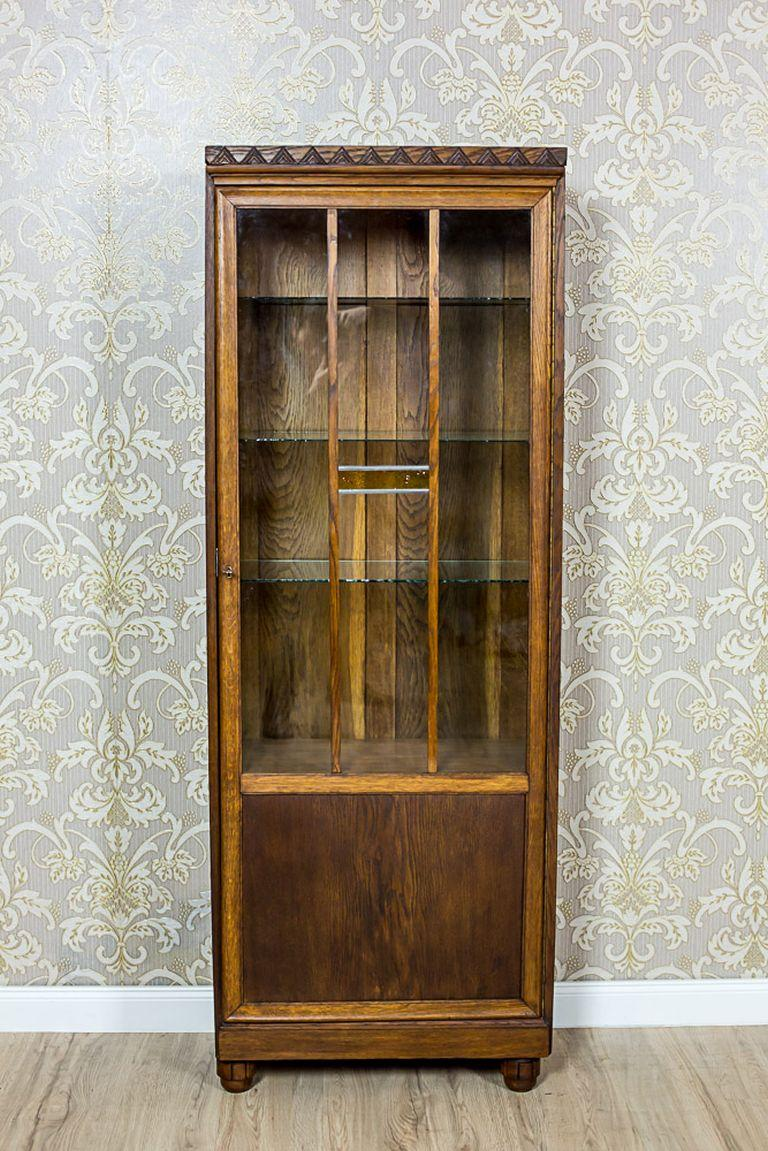 A small, one-door piece of furniture, circa 1930, with a glazed door. This amazing bookcase is made in oak and oaken burl. The simple shape of the bookcase has been varied only by a geometrical ornament on the top, and an insert of colored glass