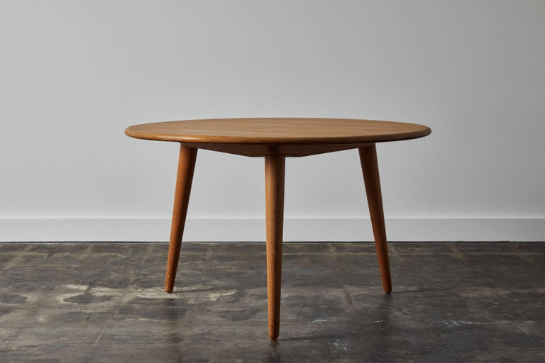Patinated oak tripod cocktail table by Hans Wegner for Andreas Tuck. Made in Denmark, circa 1950s.