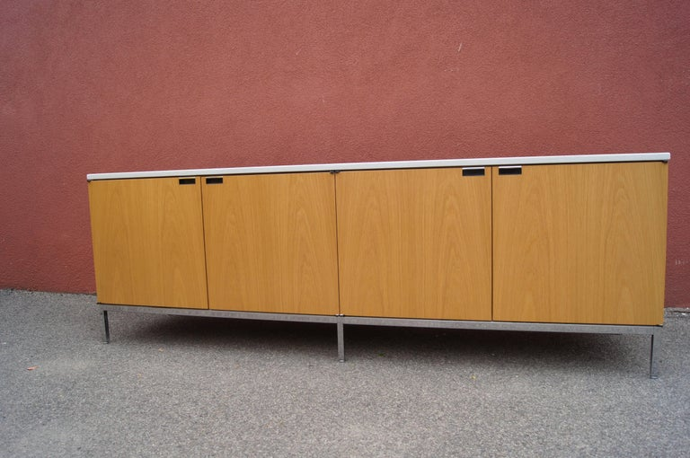 Designed by Florence Knoll in 1961, this handsome credenza comprises a light oak case on a chrome base with a marble top in