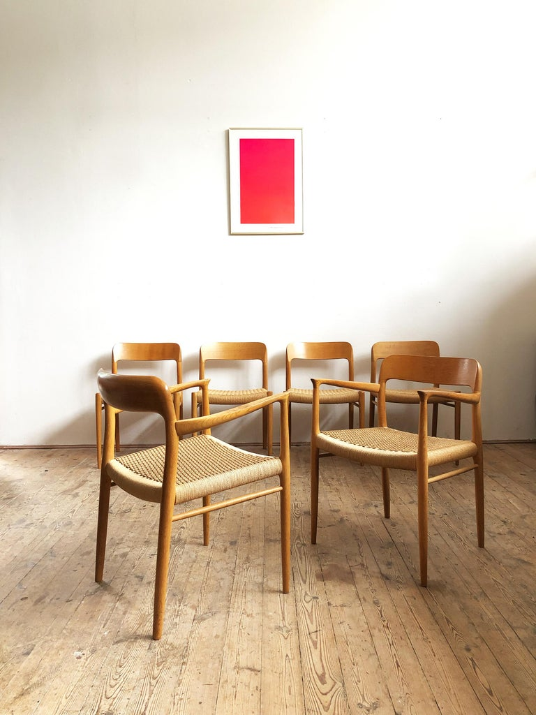 This beautiful set of dining chairs designed by Niels O. Møller was manufactured by J.L. Møllers in Denmark. The set features 2 very rare chairs model 56 with Armrests and 4 chairs model 75.   The model 56 was one of Niels Moller's earliest