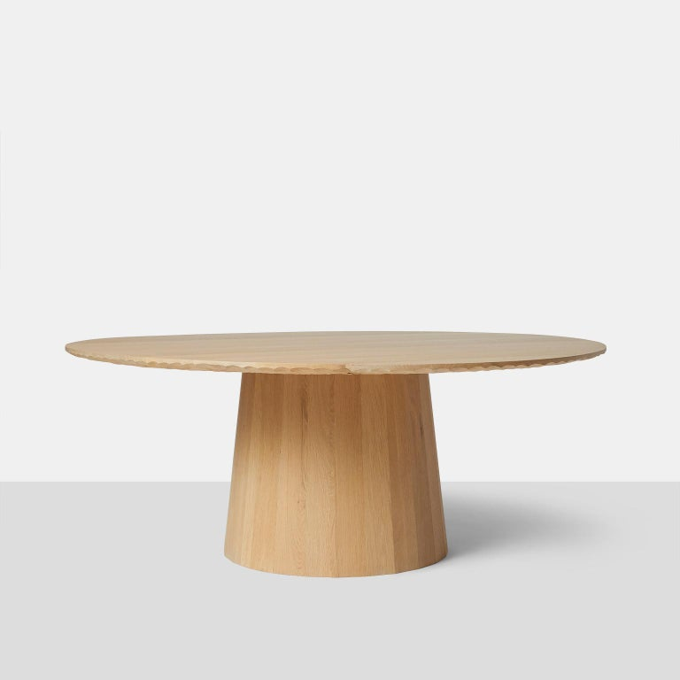 Oak dining table by Kaspar Hamacher A large round dining table in oak completely handmade with hand scraped detail on edge and underside of tabletop. The base is made with wide planks and in a circular shape. Table will accommodate 10