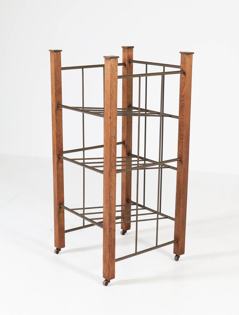 Rare extra large Art Deco Haagse School magazine stand. Striking Dutch design from the 1920s. Solid oak with brass. Original wheels in good working order. In good original condition with minor wear consistent with age and use, preserving a