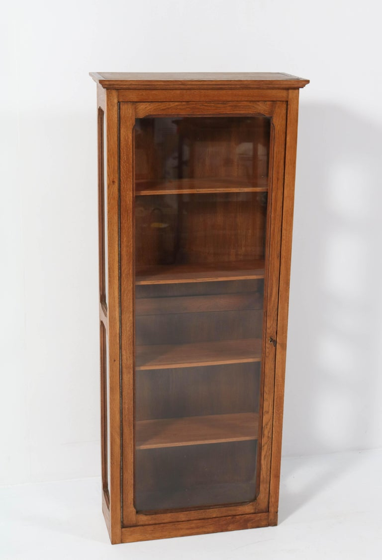 Stunning Art Nouveau wall display cabinet. Striking French design from the 1900s. Solid oak with four original wooden shelves. In very good condition with minor wear consistent with age and use, preserving a beautiful patina.