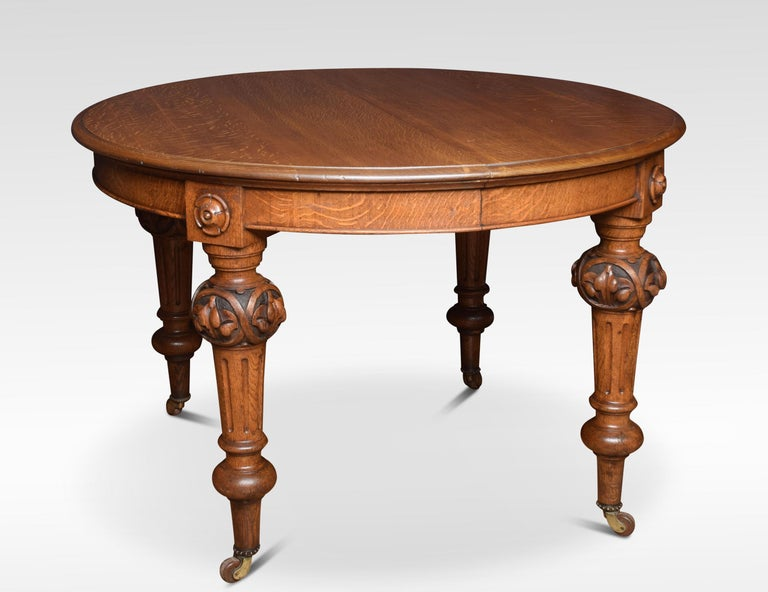 Oak extending dining table, the oval top fitted with telescopic action opening to incorporate two original additional leaves. Raised up on leaf carved and fluted legs with brass caps and casters. Dimensions Height 31 inches Width 48 inches when