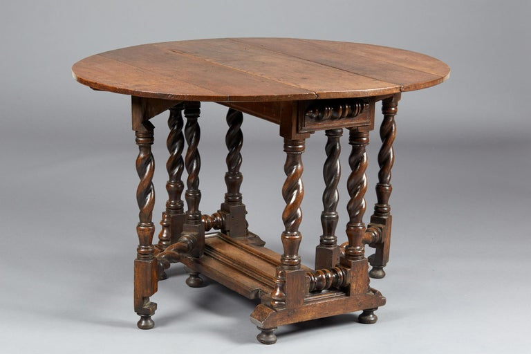 Rare Charles II / William & Mary oak gate leg table, English, circa 1670-1690.  The oval plank top above multi spiral twist legs with twin concealed action frieze drawers with applied split balusters, on a platform base with raised cushion
