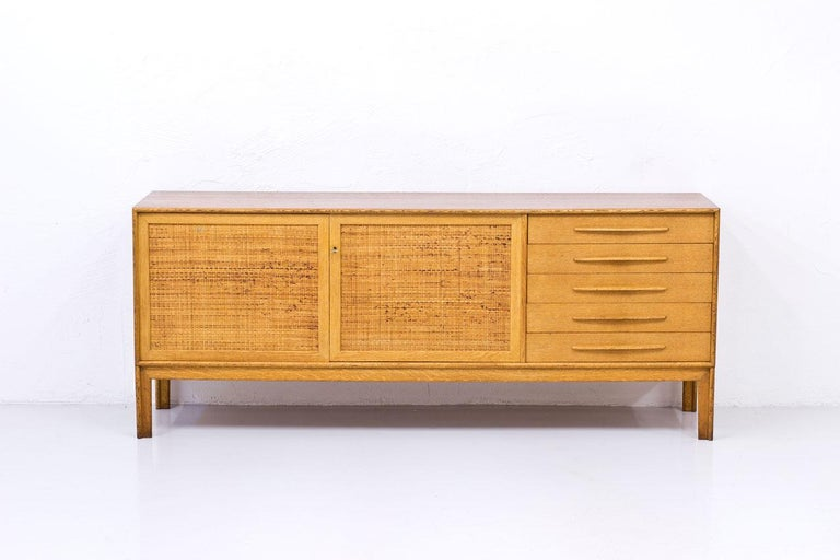 """""""Norrland"""" sideboard, large version designed by Alf Svensson for Bjästa Möbelfabrik.  Dated 12 February 1962. Made from oak with two doors panel covered by rattan webbing.  Inside in birch with adjustable shelves.  Stamped by maker."""