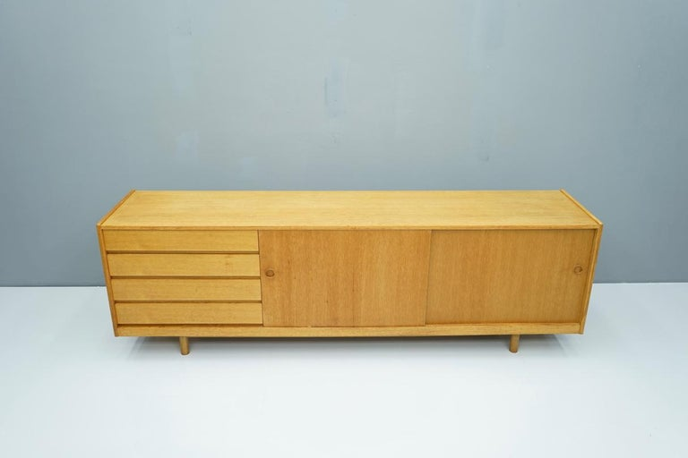 Low oak sideboard with two sliding doors and four drawers, Denmark, 1960s. Good original condition.