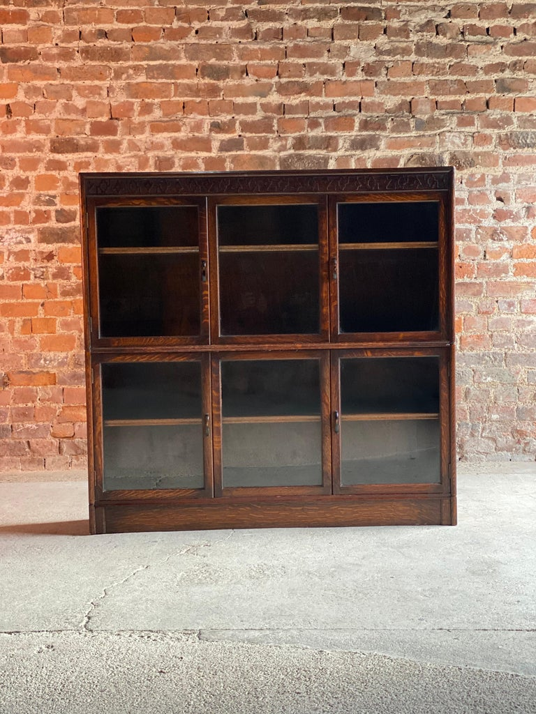 Oak stacking bookcase by Gunn USA 1920  Magnificent 1920s oak sectional bookcase by Gunn, the rectangular top with patterned relief over four doors with two central sliding panels all with original glass panels, two long adjustable shelves within,